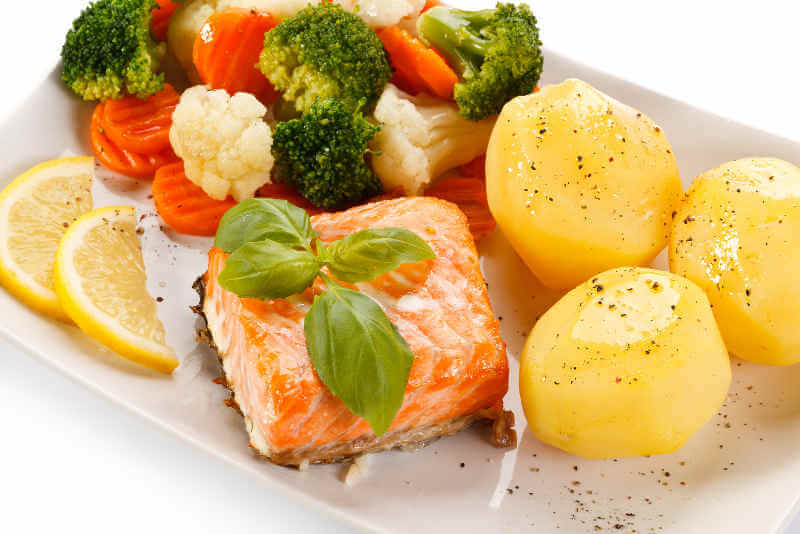 Plate of grilled salmon, potatoes and vegetables